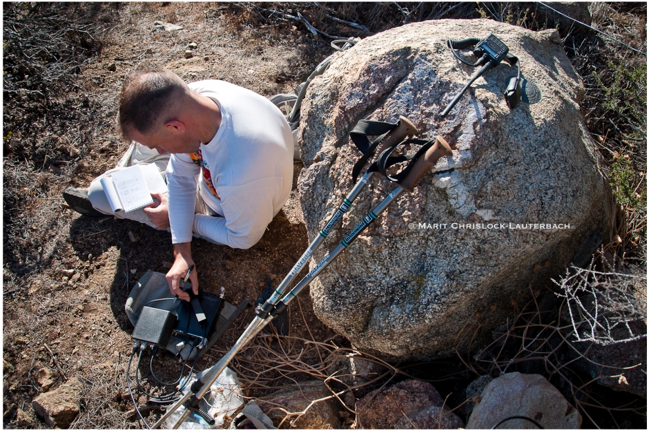 N doing morse code for Summits on the Air, with a survey marker under his radio. Naturally